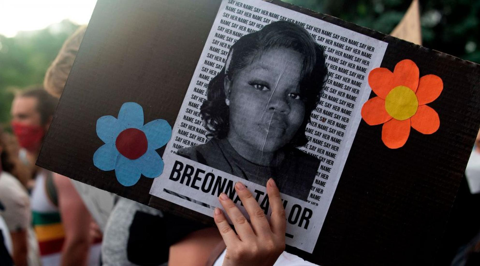 A demonstrator holds a sign with the image of Breonna Taylor