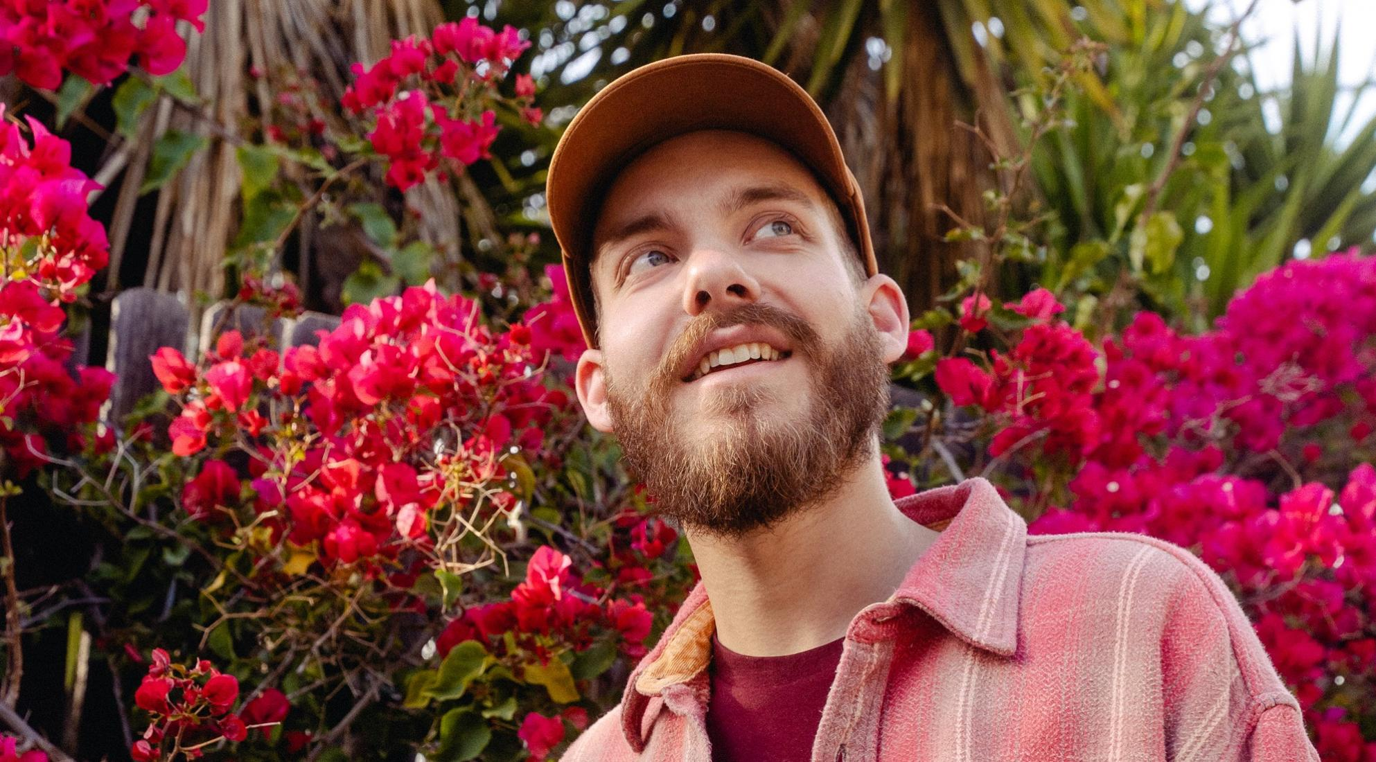 San Holo smiles in front of flowers