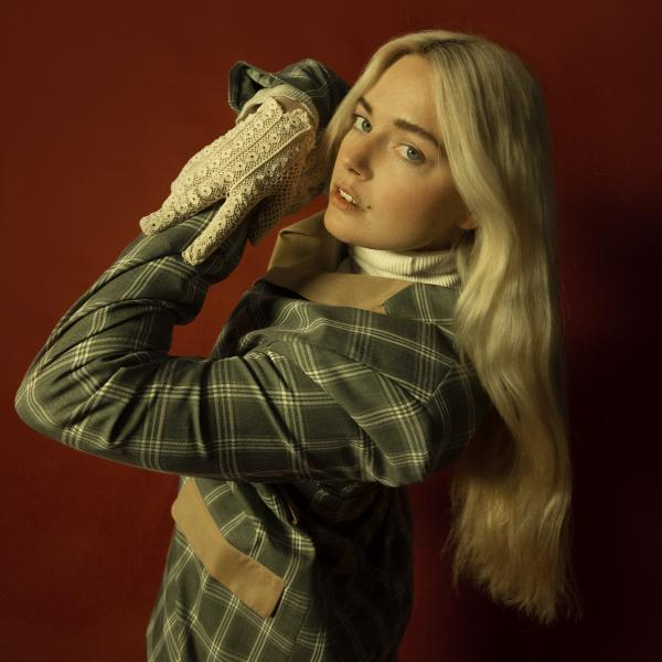 Ashe poses in a green plaid jacket & white lace gloves