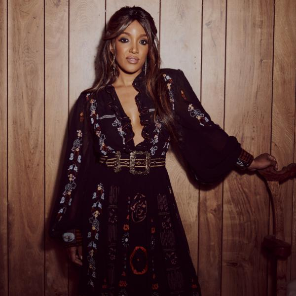 Mickey Guyton poses in a black dress
