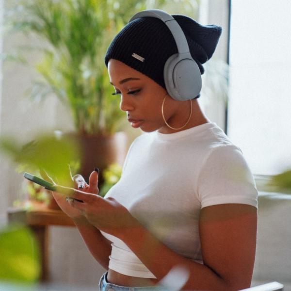 a woman listens to music with headphones