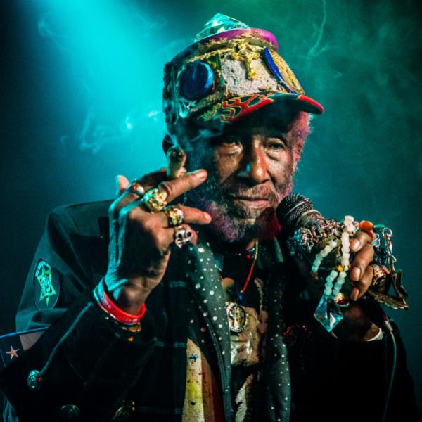 """Lee """"Scratch"""" Perry wears a colorful hat and many rings while on the mic"""