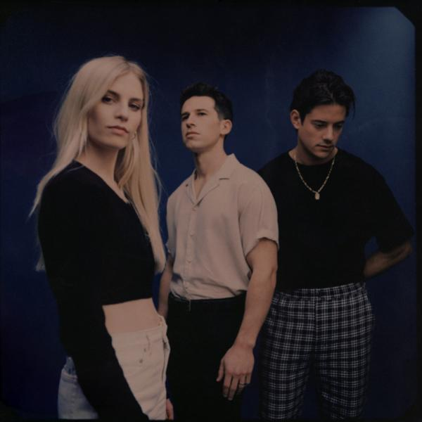 U.K. trio London Grammar pose in front of a dark background