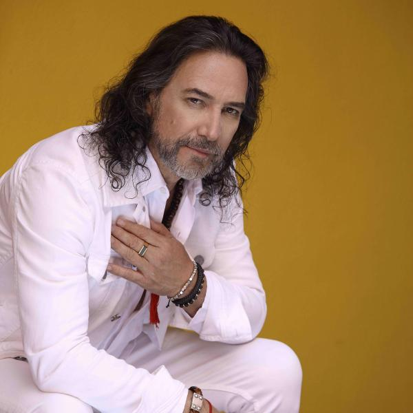 Marco Antonio Solís poses with hand on heart in all-white outfit