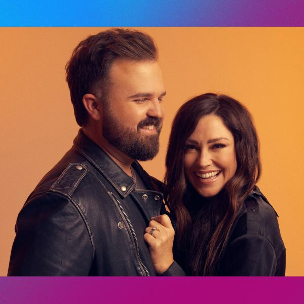 Kari Jobe and Cody Carnes smiling in front of colorful backdrop