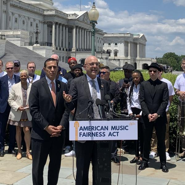 Photo of (C) Rep. Ted Deutch (D-Fla.) speaking at the U.S. Capitol and (L) Rep. Darrell Issa (R-Calif)