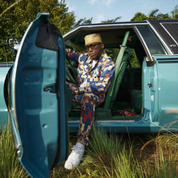 Spinall poses in a turquoise car parked in a grassy field