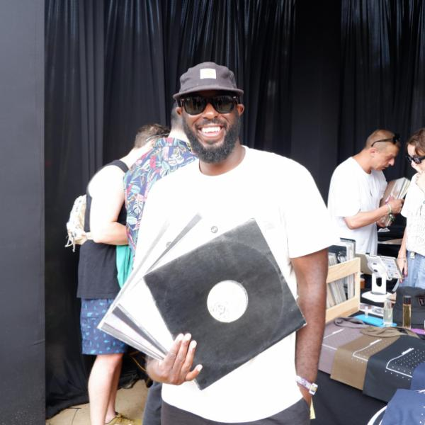 T.Williams holds up his vinyl selects in front of the Stellar Remnant pop-up at CRSSD Festival 2021