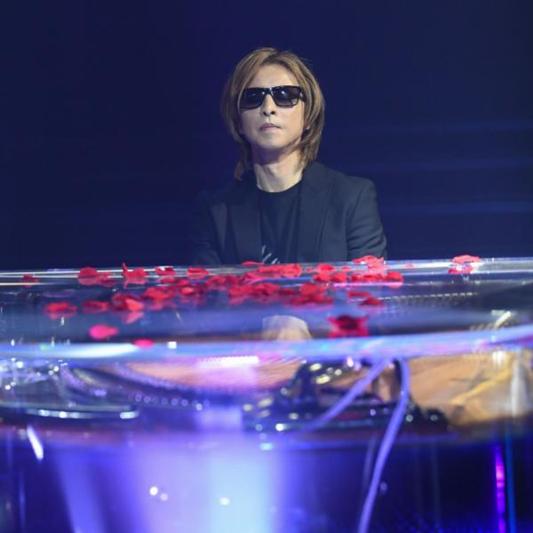 Yoshiki performs at a clear piano with rose petals on it