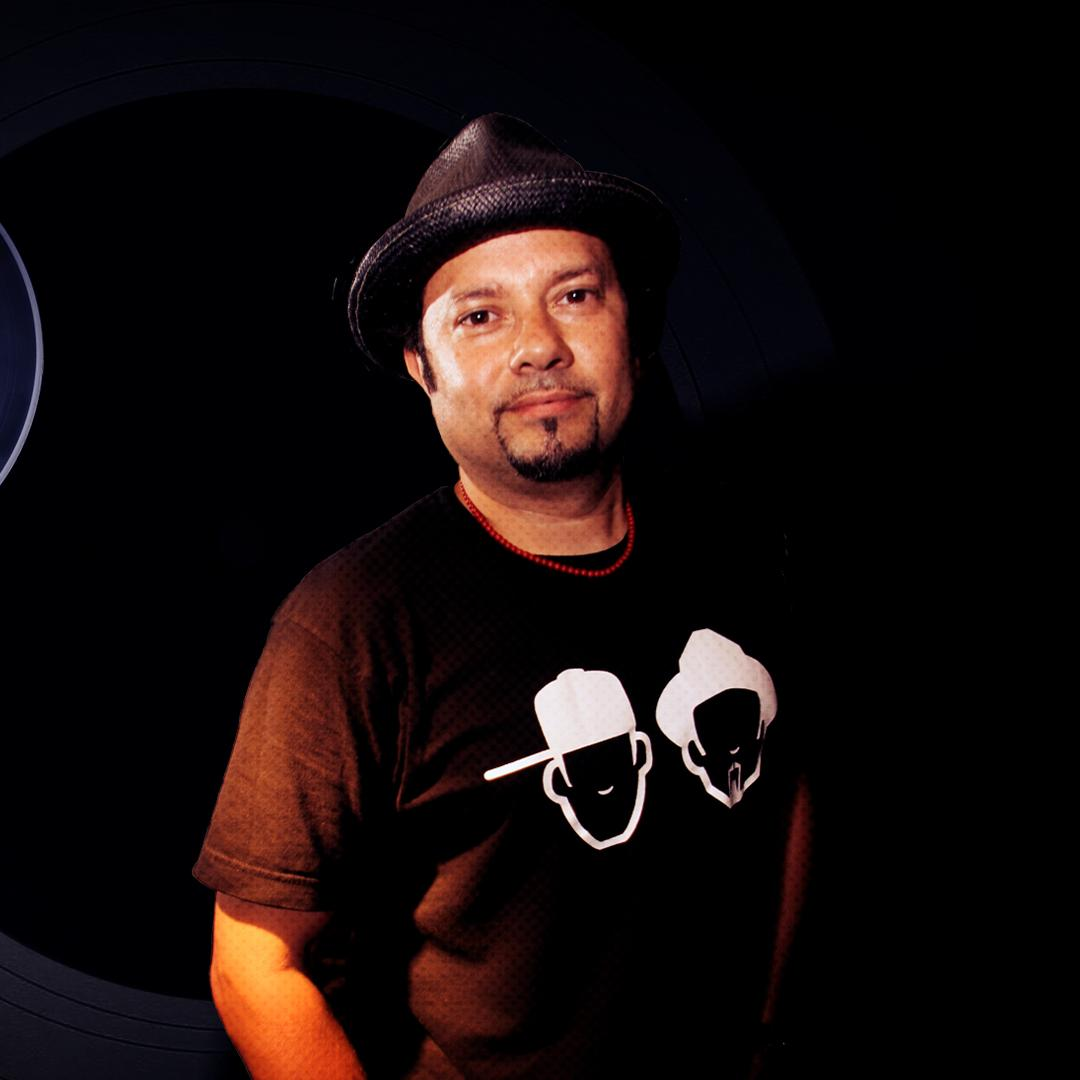 """""""Little"""" Louie Vega smiles at the camera while wearing his merchandise"""
