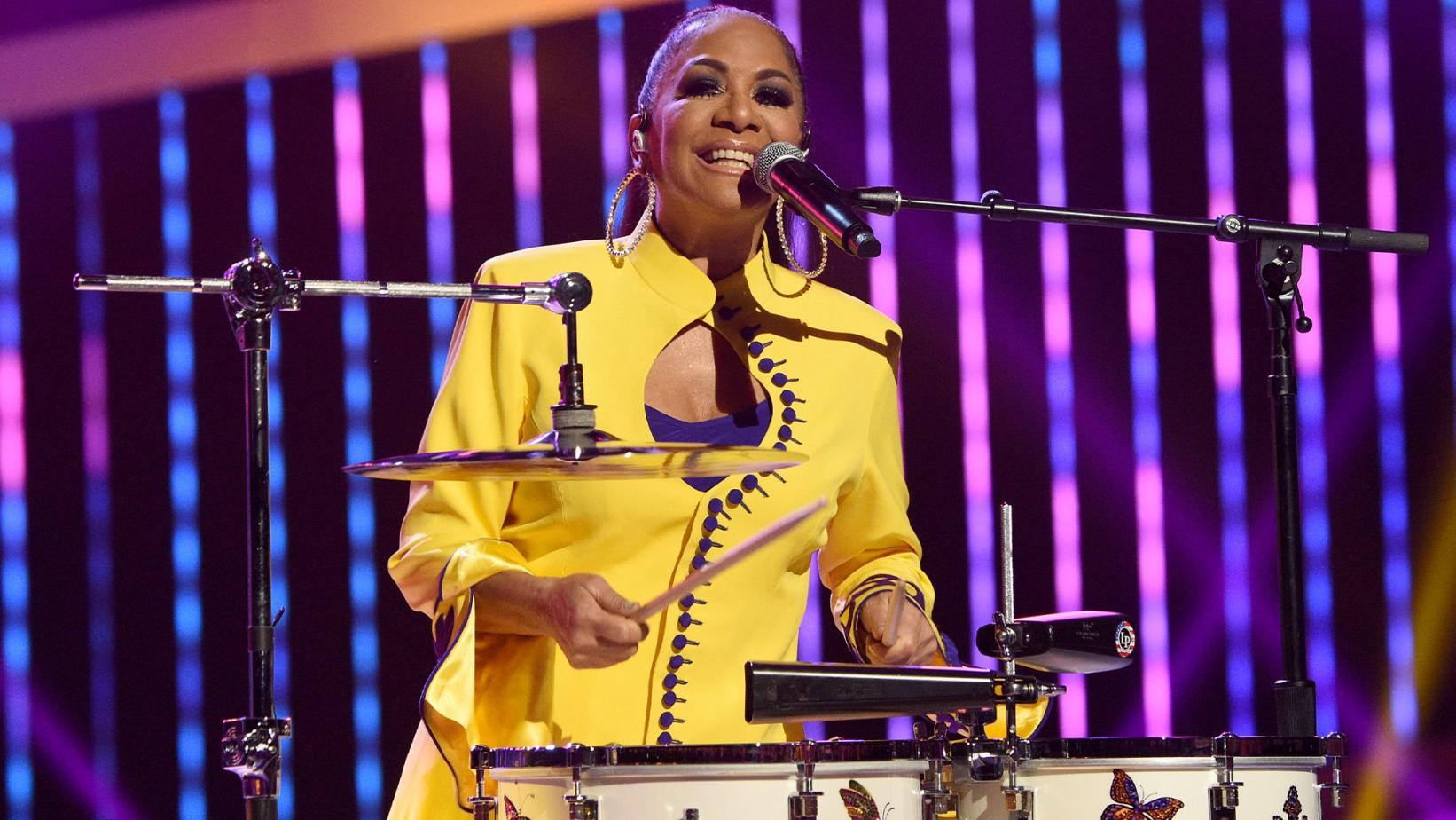 Sheila E. smiling while playing the drums and singing