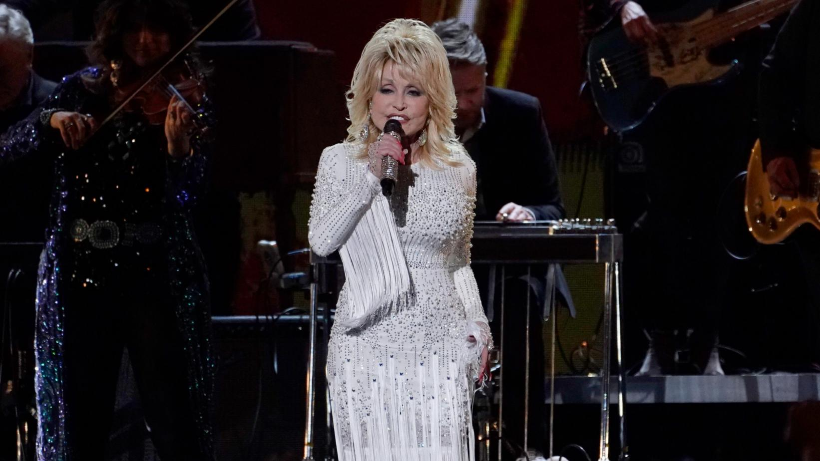 Dolly Parton sings on stage in a white fringed dress