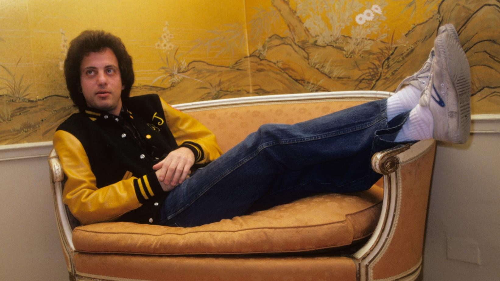Billy Joel laying on a couch backstage Madison Square Garden