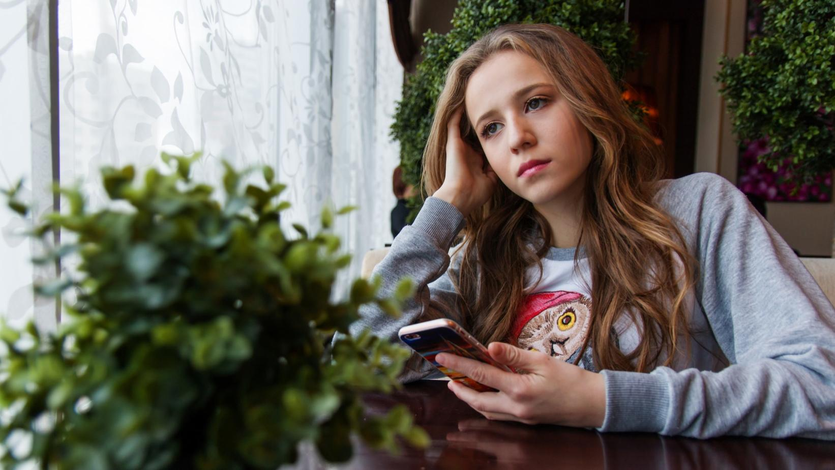 Sad looking teenage girl holding phone in hands
