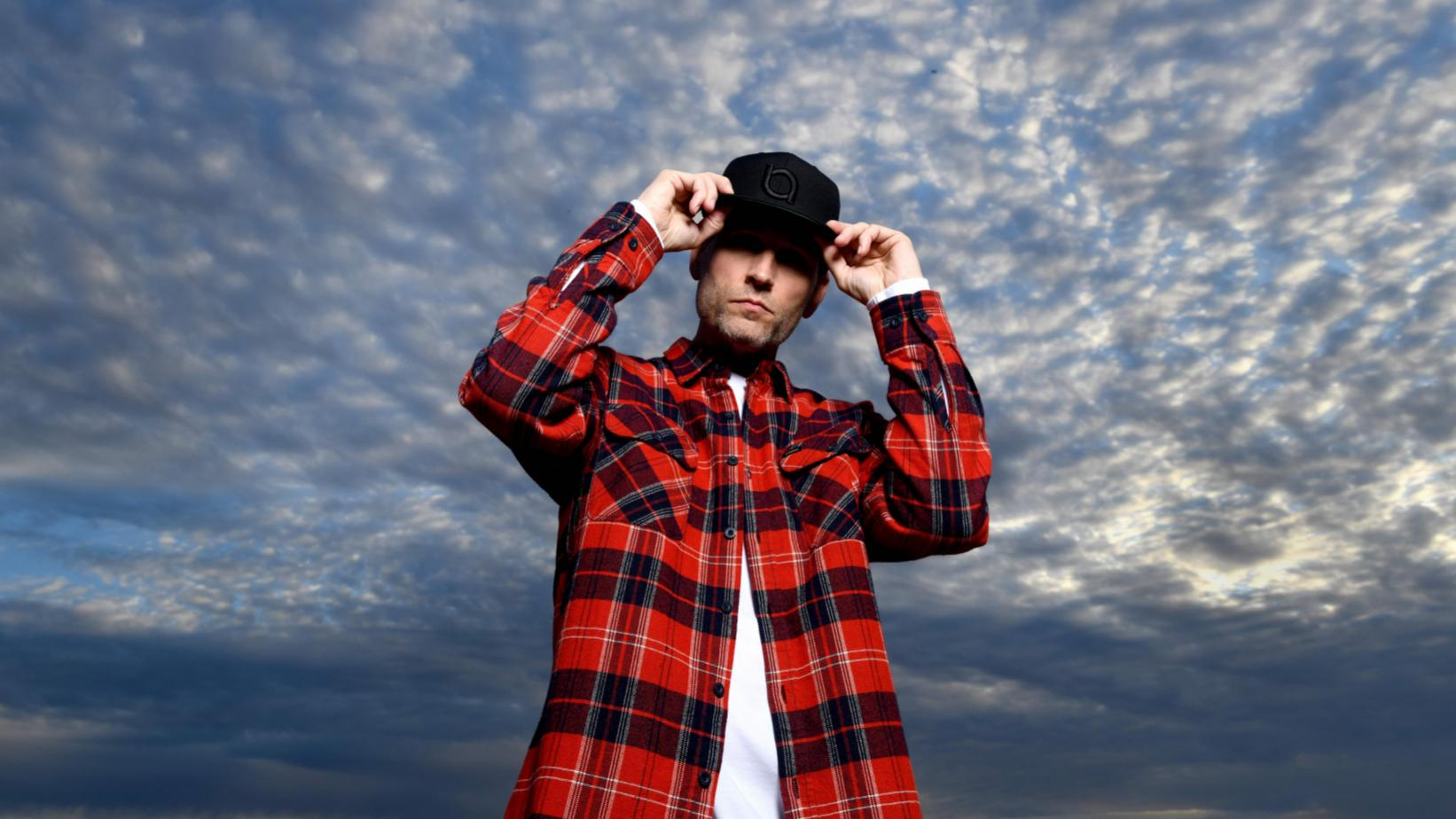 Kaskade stands in front of a cloudy blue sky