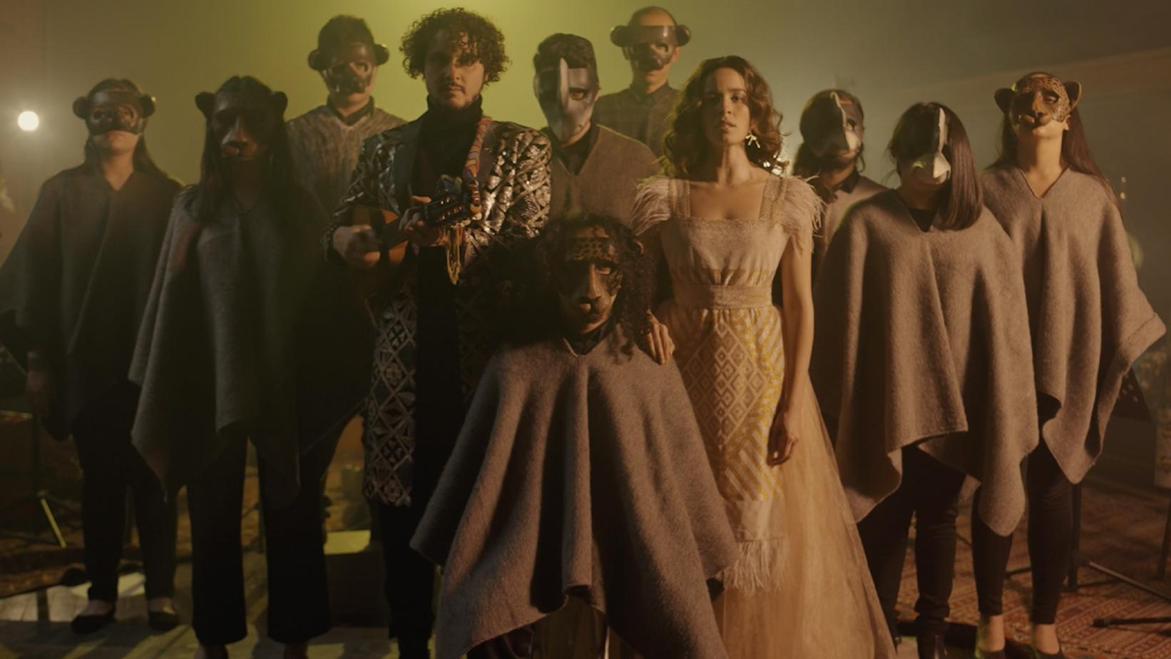 Monsieur Periné poses with their band, who are wearing animal masks