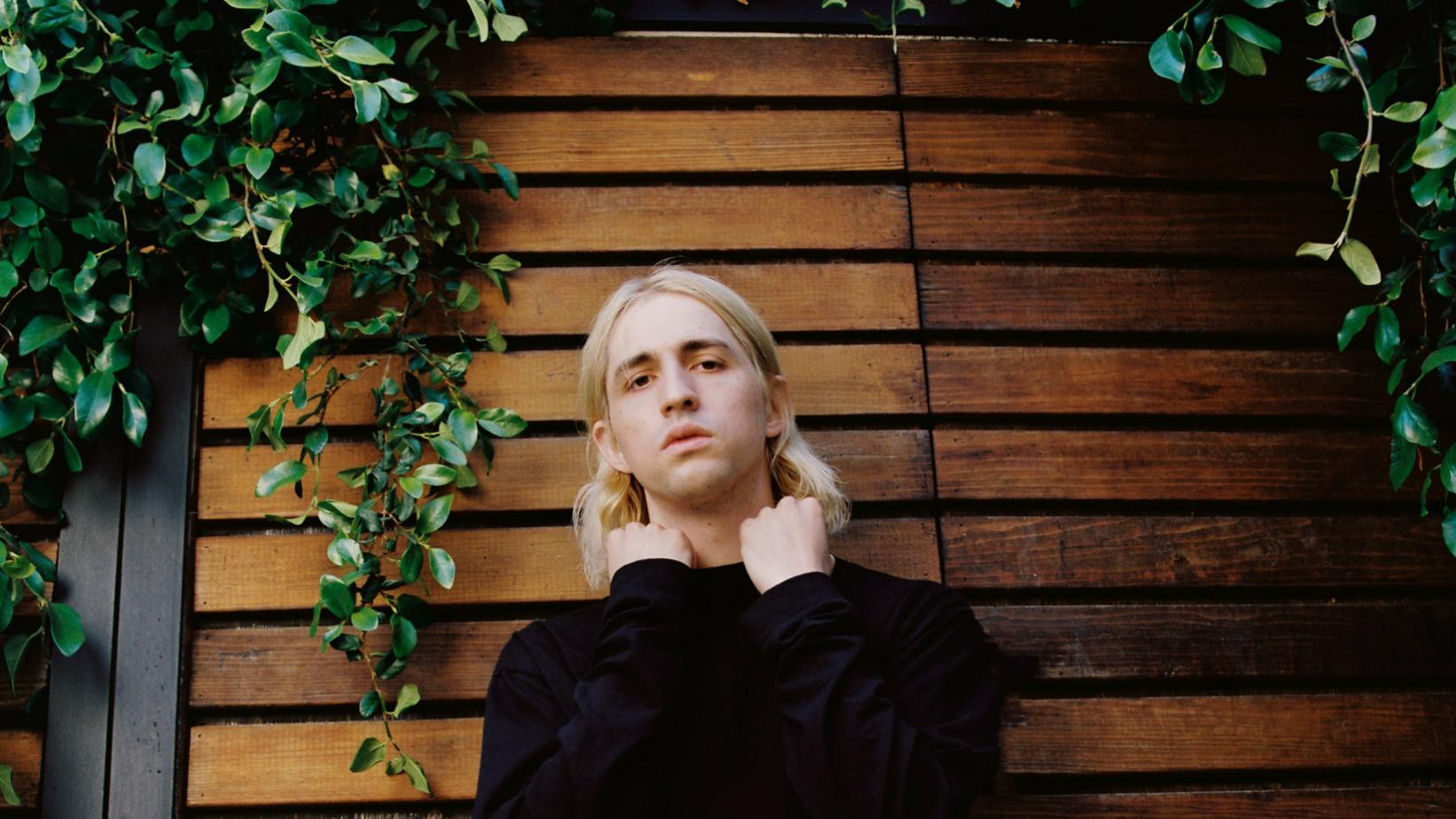 Porter Robinson poses in all-black, in front of a vine-covered fence