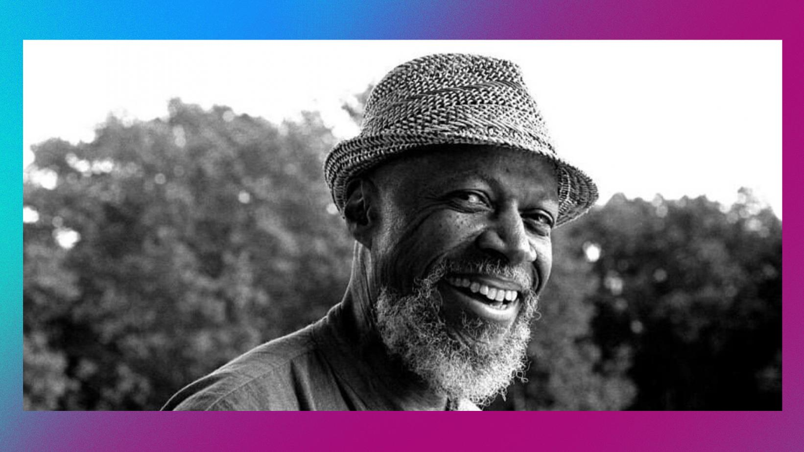 black and white photo of Laraaji smiling with a straw hat