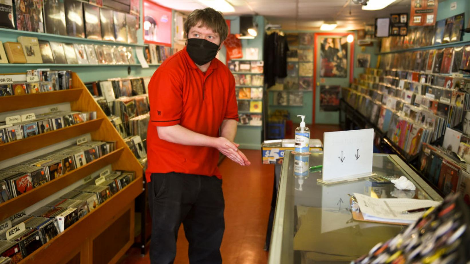 Nick Demangone of Exeter Township sanitizes his hands before browsing records for sale at Vertigo Music in West Reading