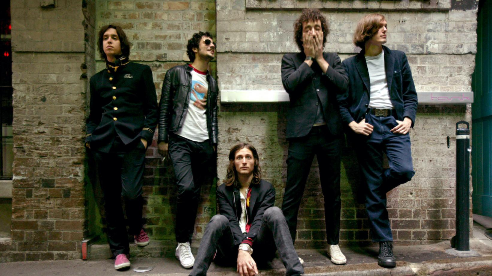 The Strokes positioned in front of a brick wall