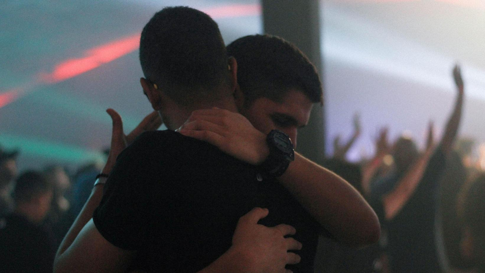 two people hug in the crowd of a concert